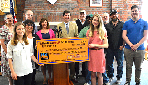 Mark C. Poloncarz stands with supports presenting a check